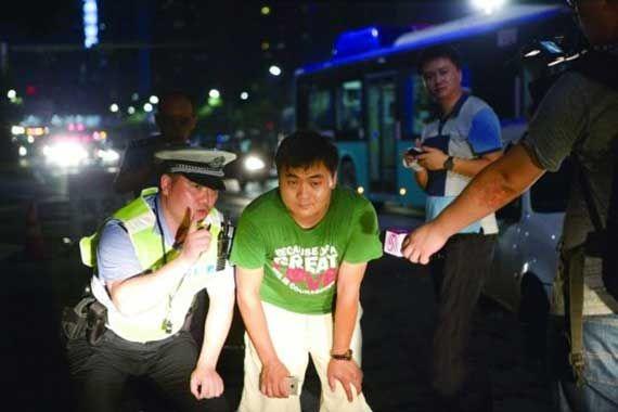 深圳交警让一名男司机半蹲在自己车头前观察远光灯的威力