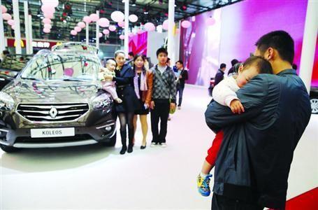 2013年上海车展,有观众怀抱小孩边拍照边观展。晨报记者殷立勤