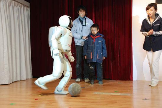 图为ASIMO与都江堰小学生一同踢球