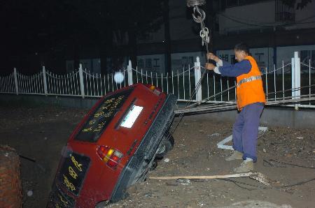 组图:北京市政公司人员吊起陷入坑中车辆