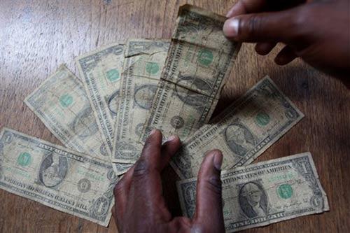 哈拉雷的一名男子在清洗美元纸币前仔细清点。