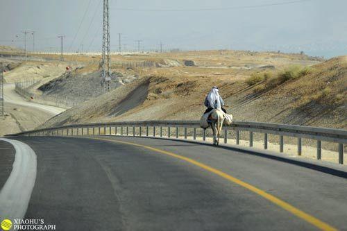 我们的汽车在约旦河西岸地区的公路上行驶,路边骑毛驴的巴勒斯坦老头,可以看到沿着公路延绵不绝的铁丝网