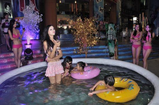 2013年8月16日,武汉闹市街头,几位身着比基尼的美眉在充气泳池中戏水清凉亮相,为酒吧派对吸睛。