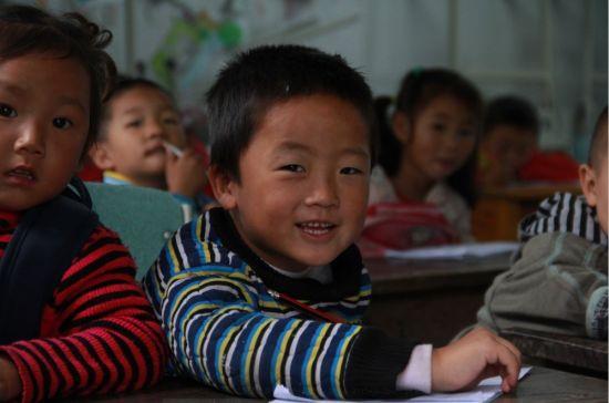 七家村村小今年毕业的孩子们有着非常不平凡的经历五年内,他们经历过两次地震, 512汶川地震和420芦山地震。420地震后,七家村村小校舍已经成为危楼,不能继续使用。在新校舍重建的日子里,孩子们集中在九间板房中继续他们的学业。朗朗的读书声不绝于耳,追跑游戏的身影充斥着红砖铺就的临时校园。虽然条件比较艰苦,但学校依然在尽最大的努力让孩子们保持着正常的课业进程。新校舍将在明年秋季落成,谈到如何让孩子们在薄薄的板房中度过即将到来的冬季,张校长表示学校会想办法,孩子们也会坚持。   张校长个子不高,头发