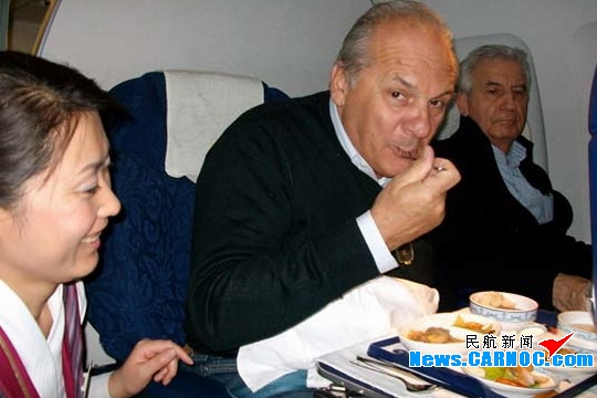乘务员向国际友人征求对机上餐食的意见