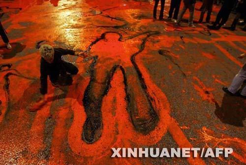 12月8日,在希腊首都雅典,示威者在地上涂抹红色和黑色,象征死者和鲜血。新华社/法新