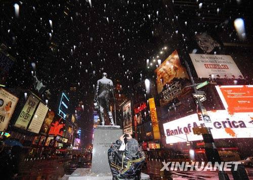 3月1日晚,在美国纽约时报广场,一位男士在雪中拍摄照片。新华社记者申宏摄