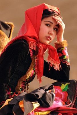 3月27日,在新疆鄯善县库木塔格沙漠公园,一名维吾尔族姑娘在为摄影爱好者当模特。