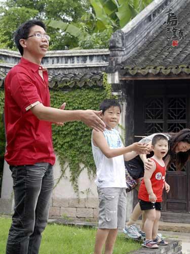一位爸爸亲自示范着教儿子玩他小时候的竹蜻蜓