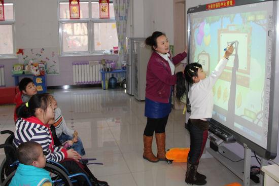 图一 儿童福利院老师用新设备教学