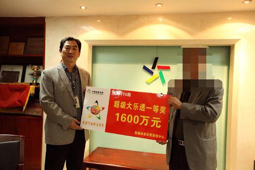 新疆体育彩票管理中心副主任焦一霖为1600万元大奖得主颁发奖金。