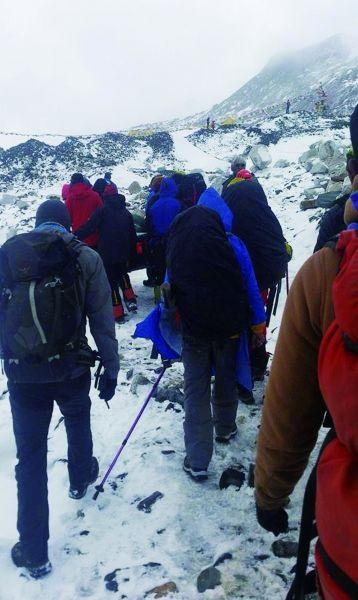爬山者和导游抬着在珠峰雪崩中受伤的职员撤退图/IC