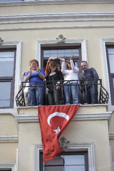 图文-奥运会圣火在伊斯坦布尔传递 聚在阳台助威