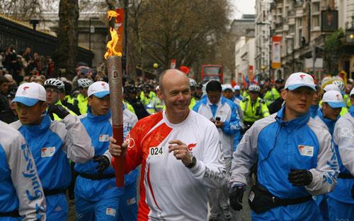 图文-奥运圣火在伦敦传递 前橄榄球队教练传递圣火