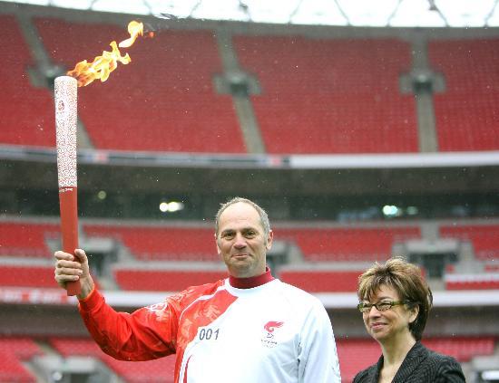 图文-奥运圣火在伦敦传递 首棒手持火炬微笑展示