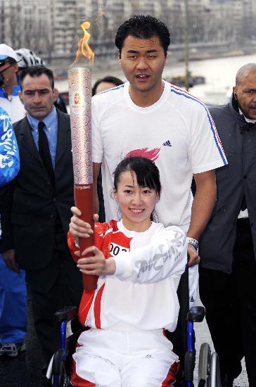 图文-北京奥运圣火在巴黎传递 金晶手持火炬传递
