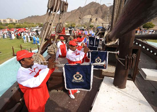 图文-圣火传递在马斯喀特举行 吹奏当地特色乐器