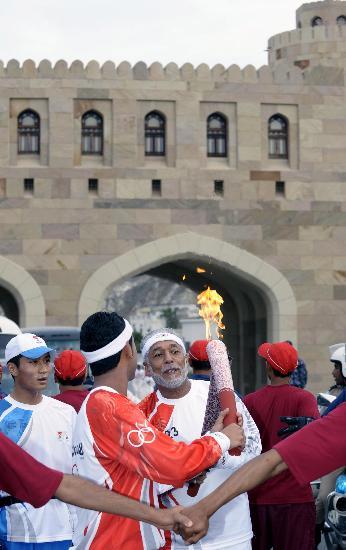 图文-圣火传递活动在马斯喀特举行 火炬手进行交接