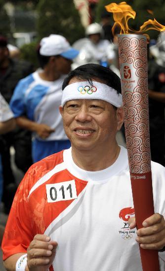 图文-奥运圣火在吉隆坡传递 圣火映红火炬手脸庞