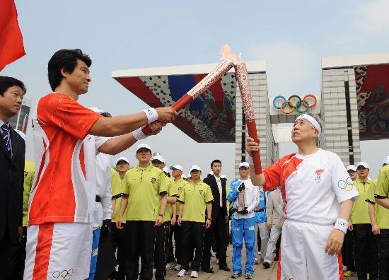 图文-北京奥运圣火在首尔传递 金正吉与文大成交接