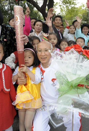 图文-北京奥运会火炬在平壤传递 小朋友触摸火炬