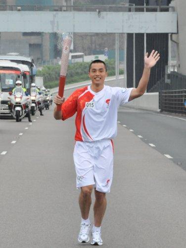 图文-北京奥运圣火在香港传递 火炬手余庆龙招手