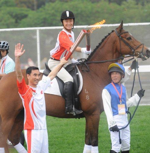 图文-北京奥运圣火在香港传递 马背上的圣火交接