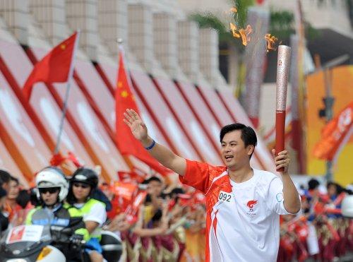 图文-北京奥运圣火在香港传递 火炬手黄建恒挥手