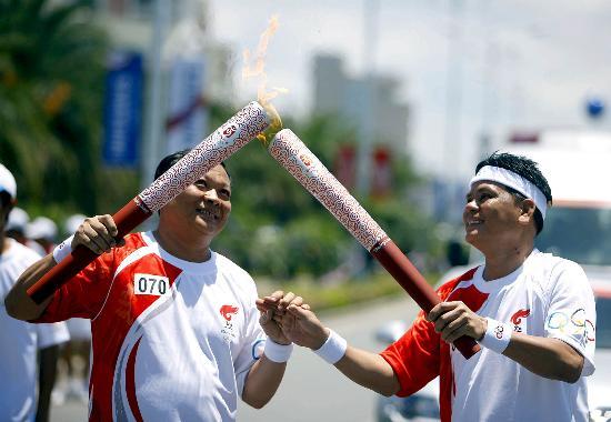 图文-北京奥运圣火在三亚传递 陆文良与吴乾章交接