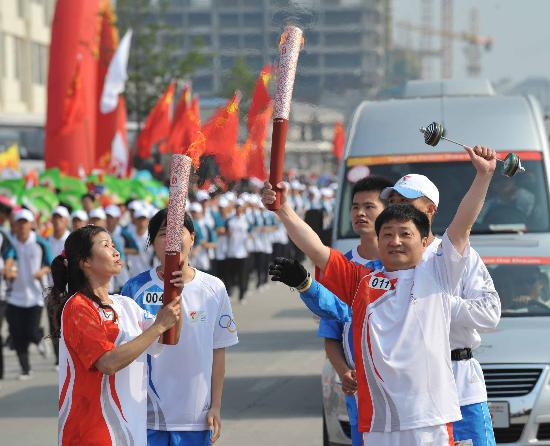 图文-北京奥运圣火在龙岩传递 夫妻火炬手进行交接