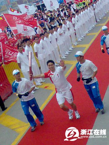 图文-奥运圣火在宁波传递 首棒火炬手微笑起跑