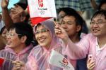 图文-奥运圣火在重庆万州传递 重庆群众冒雨助威