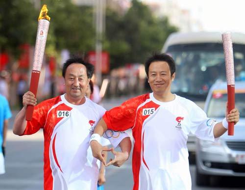 图文-北京奥运圣火在喀什传递 火炬手合做桃心手势
