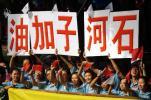 图文-奥运圣火在新疆石河子传递 群众打出标语助威