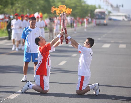 图文-奥运圣火在甘肃嘉峪关传递 双膝跪地交接