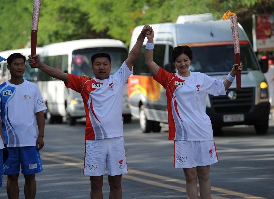 图文-北京奥运圣火在嘉峪关传递 完成交接双手紧握