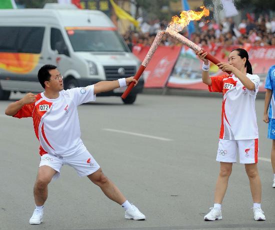 图文-奥运圣火在松原市传递 张辉与马永明交接