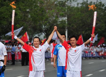 图文-奥运圣火在鞍山传递 两名火炬手交接圣火