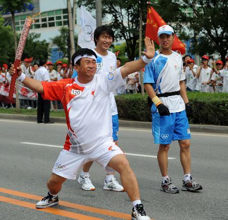 图文-奥运圣火在鞍山传递 这个动作在电影里很常见