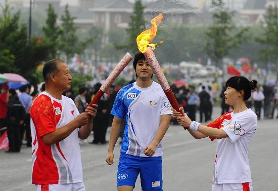 图文-北京奥运圣火在大连传递 王霖与岳金库交接