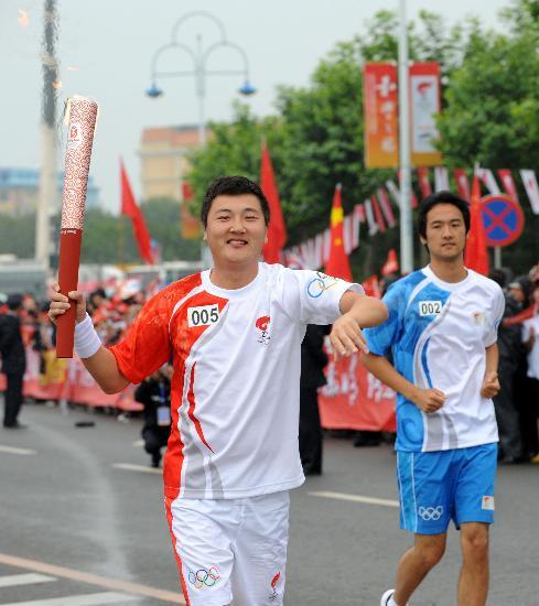 图文-奥运圣火在大连传递 著名歌手孙楠微笑传递