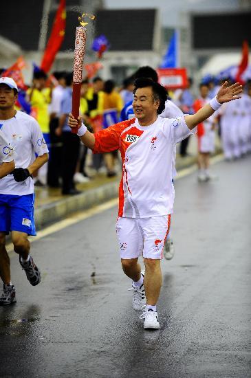 图文-北京奥运圣火在大连传递 火炬手李传声挥手
