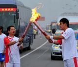 图文-北京奥运圣火在临沂传递 陈涛与金延财交接