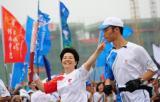 图文-奥运圣火在济南传递 刘秀稳手持火炬传递