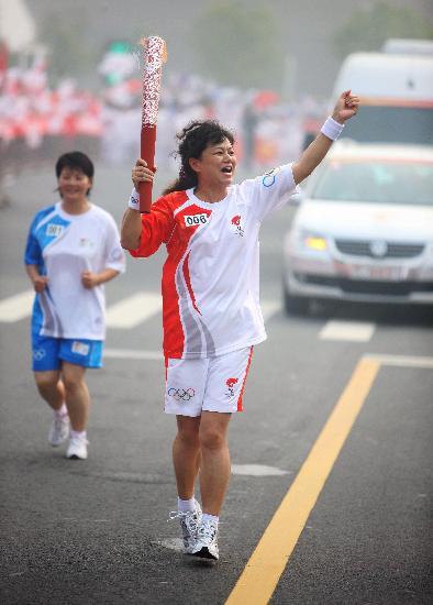 图文-奥运圣火在郑州传递 巫兰英手持火炬传递