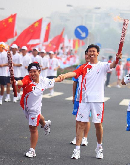 图文-北京奥运圣火在郑州传递 冯志敏与鹿豫交接