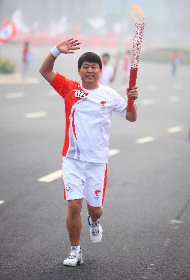 图文-奥运圣火在郑州传递 热情向观众们挥手
