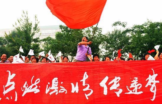 图文-奥运圣火在安阳传递 群众挥舞旗帜为传递加油
