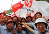 图文-奥运圣火在唐山传递 群众争相与火炬手合影