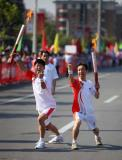 图文-奥运圣火继续在天津传递 握拳庆祝胜利交接
